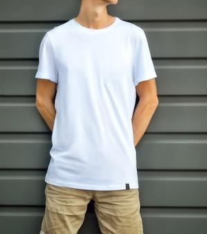 Maquete urbana de roupas. jovem encostado na parede texturizada cinza em uma camiseta em branco e shorts marrons. modelo pronto para você projetar.