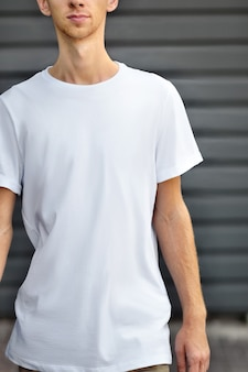 Maquete urbana de roupas. jovem vai perto da parede perfilada de metal cinza em uma camiseta em branco, rasa do dof. modelo pronto para você projetar.