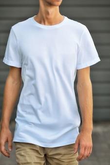 Maquete urbana de roupas. o hipster magro chega perto da parede texturizada cinza em uma camiseta em branco e shorts marrons. modelo pronto para você projetar.