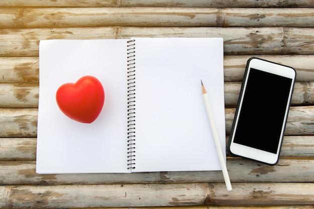 Maquete vista superior do notebook com vidro de lápis e modelo de borracha de coração na mesa de madeira de bambu