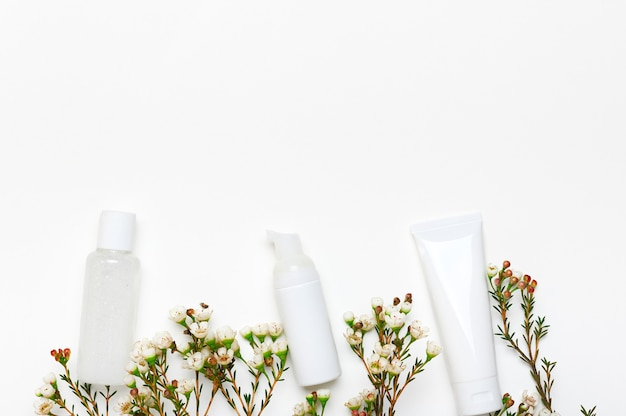 Maquetes de frascos de cosméticos em branco com fundo vazio de flores removedor de maquiagem