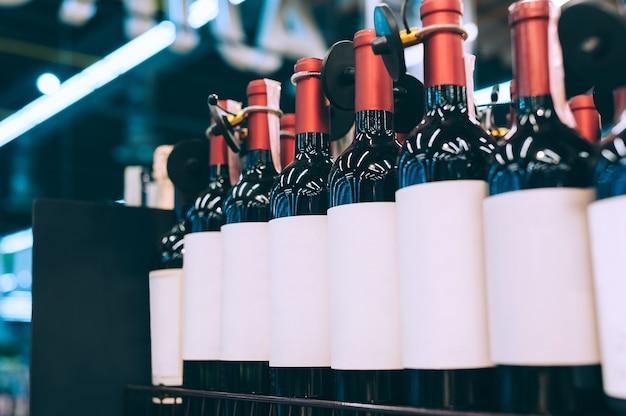 Maquetes de garrafas de vidro com vinho no balcão de um supermercado.