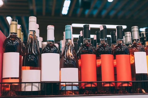 Maquetes de garrafas de vidro com vinho rosé no balcão de um supermercado.