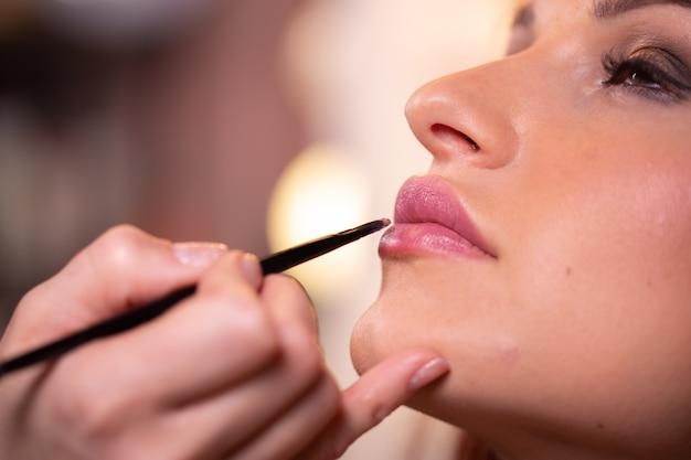 Maquiador aplica batom gloss rosa. rosto de mulher bonita. mão do mestre de maquiagem, pintando os lábios da garota de modelo de beleza jovem. maquiagem em processo
