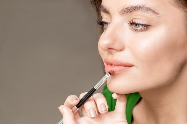 Maquiador aplica batom no rosto de uma mulher bonita, maquiagem em processo.