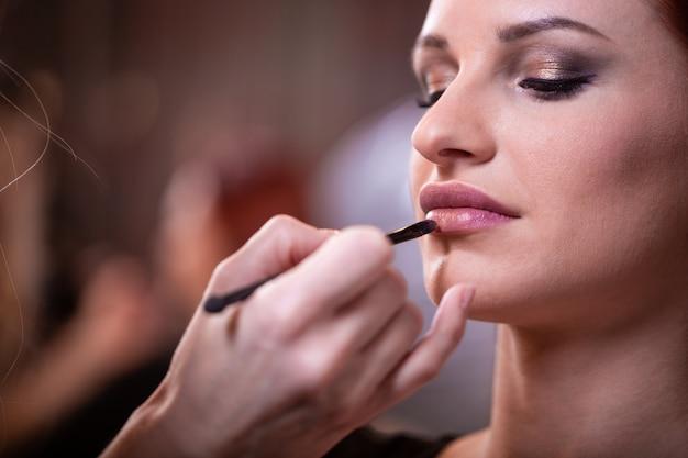 Maquiador aplica batom vermelho. rosto de mulher bonita. mão do mestre de maquiagem, pintando os lábios da garota de modelo de beleza jovem. maquiagem em processo
