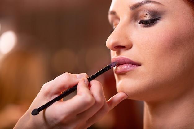 Maquiador aplica batom vermelho