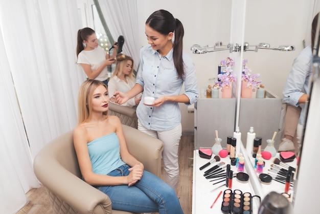 Maquiador aplica o blush para a garota com pincéis.