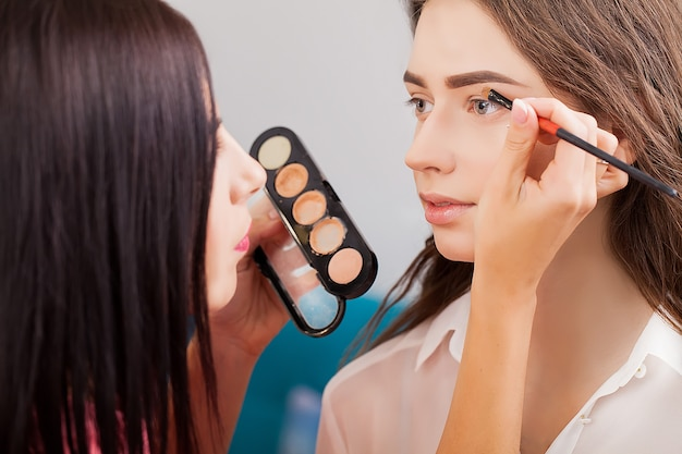 Maquiador aplica sombra nos olhos. rosto de mulher bonita. maquiagem perfeita