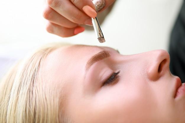 Maquiador aplica sombra para os olhos no modelo de sobrancelhas