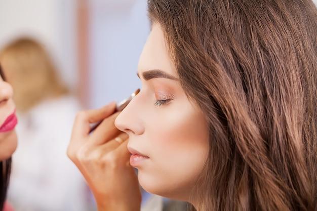 Maquiador aplica sombra para os olhos. rosto de mulher bonita. maquiagem perfeita