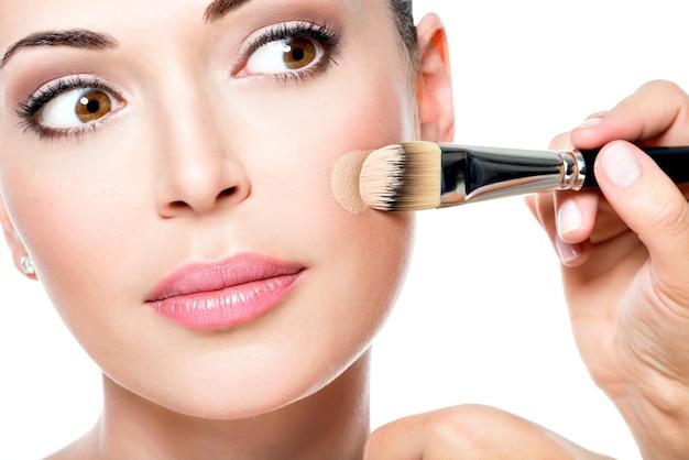 Maquiador aplicando base tonal líquida no rosto da mulher