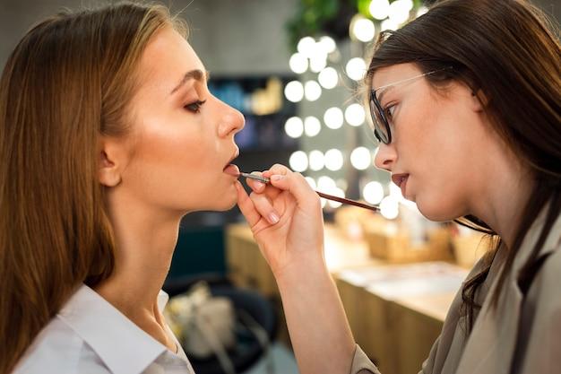 Maquiador aplicando batom na mulher