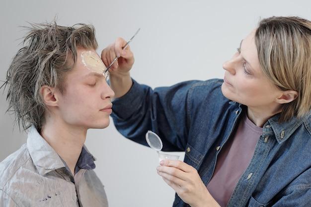 Maquiador aplicando greezepaint no rosto do empresário antes de fotografar