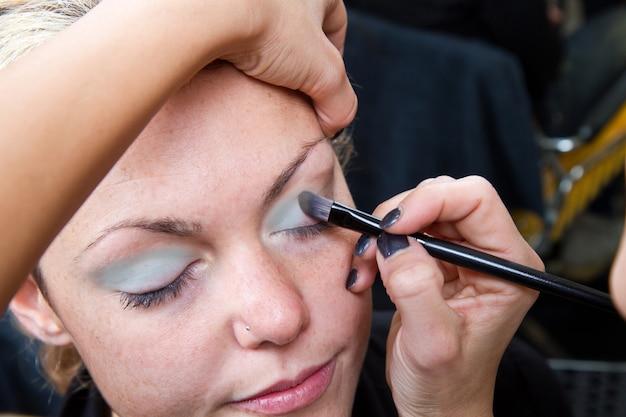 Maquiador aplicando maquiagem de sobrancelha