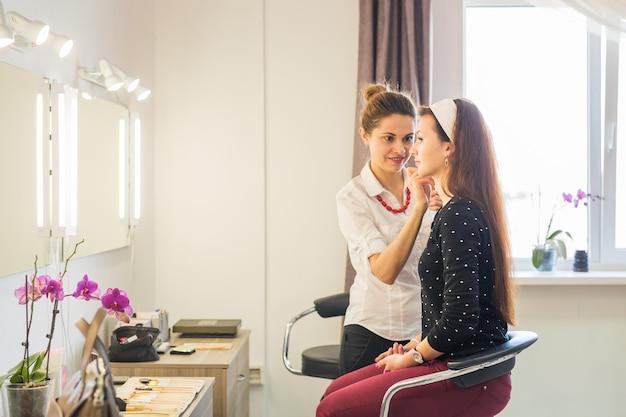 Maquiador aplicando maquiagem no modelo.