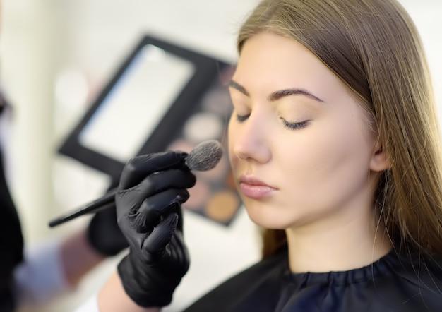 Maquiador aplicando o tom da fundação usando escova especial no rosto jovem bela modelo