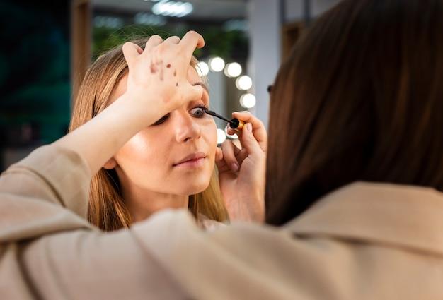 Maquiador aplicando rímel na mulher