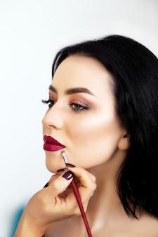 Maquiador aplicando sombra para uma mulher