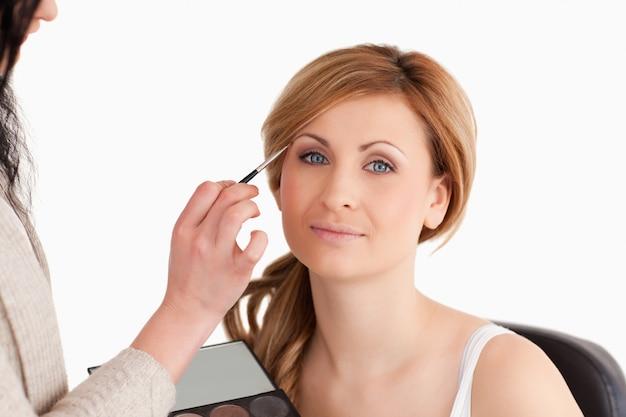 Maquiador aplicar maquiagem para uma mulher loira