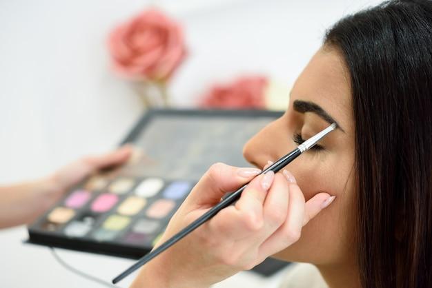 Maquiador colocando maquiagem nas sobrancelhas de uma mulher