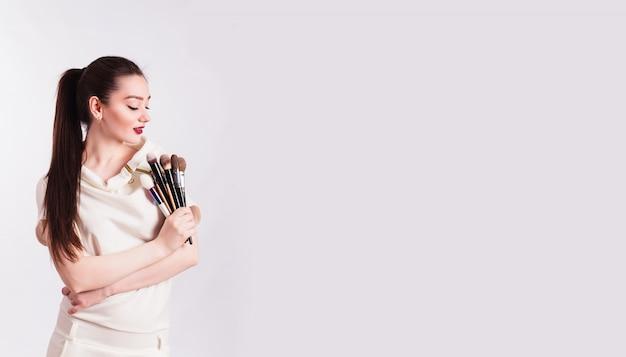 Maquiador com pincéis na mão em uma parede branca