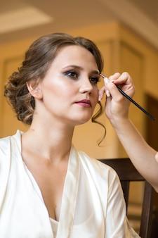 Maquiador de casamento fazendo uma maquiagem para noiva. manhã nupcial de uma senhora bonita. acusações da noiva