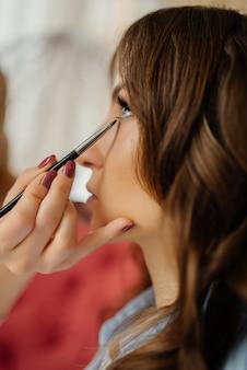 Maquiador de casamento fazendo uma maquiagem para noiva. menina linda modelo dentro de casa. retrato feminino. manhã nupcial de uma senhora bonita. conceito de preparação do casamento.