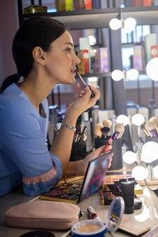 Maquiador de closeup ensinando cliente mulher a aplicar brilho labial na aula, maquie-se