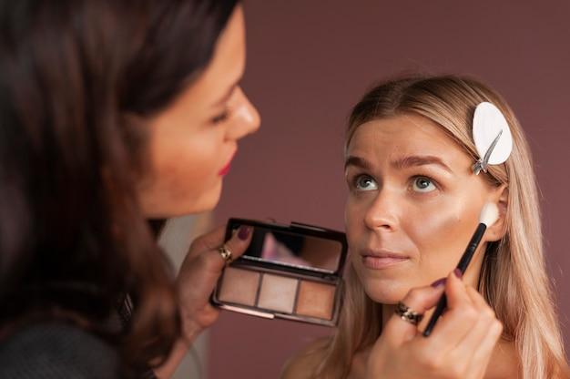 Maquiador de formação profissional mostra como usar e aplicar pó facial em uma linda modelo com pele perfeita