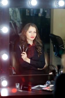 Maquiador de menina bonita perto de espelhos
