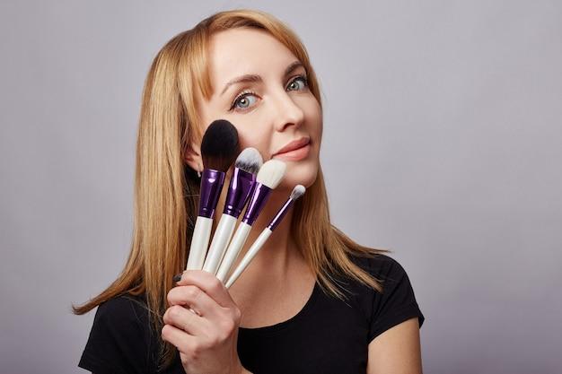 Maquiador de mulher mantém pincéis de maquiagem perto do rosto. rússia, sverdlovsk, 6 de janeiro de 2019