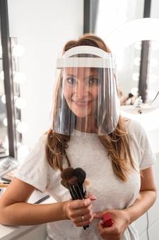 Maquiador de visão frontal com protetor facial segurando escovas