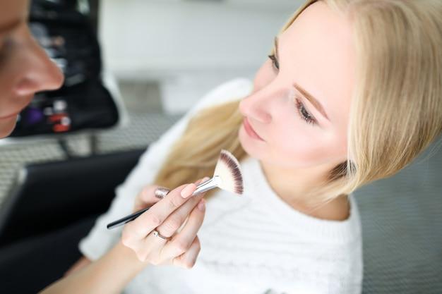 Maquiador detém escova cosmética perto modelo de rosto