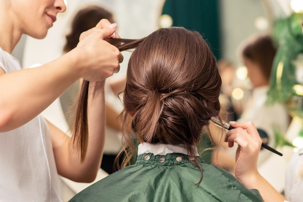 Maquiador e cabeleireiro estão preparando o penteado e o rosto de uma jovem no salão de beleza