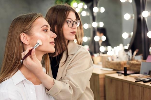 Maquiador e mulher olhando para o espelho, aplicando contorno