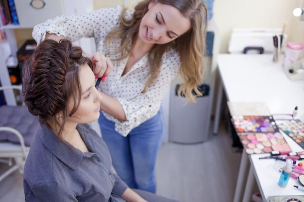 Maquiador em um salão de beleza pinta uma jovem garota bonita. uma mulher com um penteado bonito
