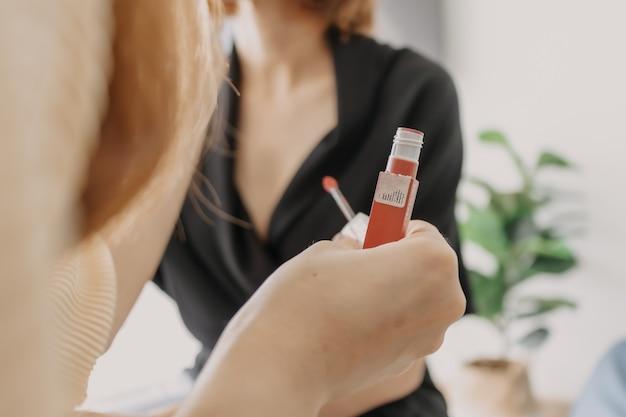 Maquiador está aplicando batom nas clientes