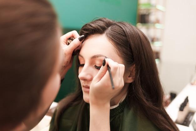 Maquiador faz maquiagem de sobrancelha para seu cliente. procedimento de desenho de sobrancelha