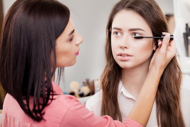 Maquiador faz maquiagem para uma garota bonita em um salão de beleza