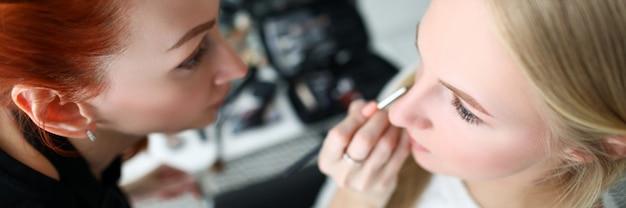 Maquiador faz rosto de maquiagem para menina loira
