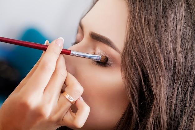 Maquiador fazendo garota de maquiagem no salão, conceito de beleza
