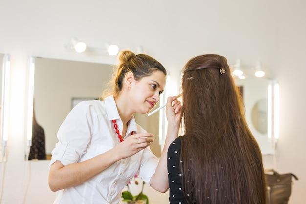 Maquiador fazendo maquiagem para jovem linda noiva aplicando maquiagem de casamento