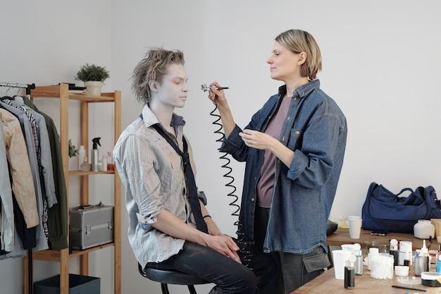 Maquiador feminino maduro aplicando tinta cinza no rosto de um homem de negócios com equipamento especial