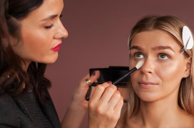 Maquiador feminino usa um pincel com bronzer para esculpir o rosto de uma mulher loira.