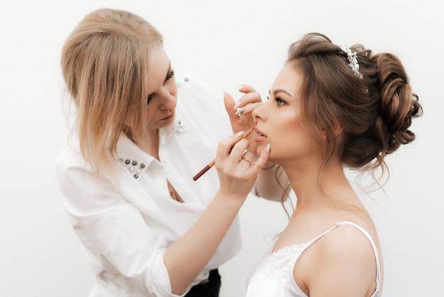 Maquiador maquiagem e pinta os lábios da noiva com um lápis