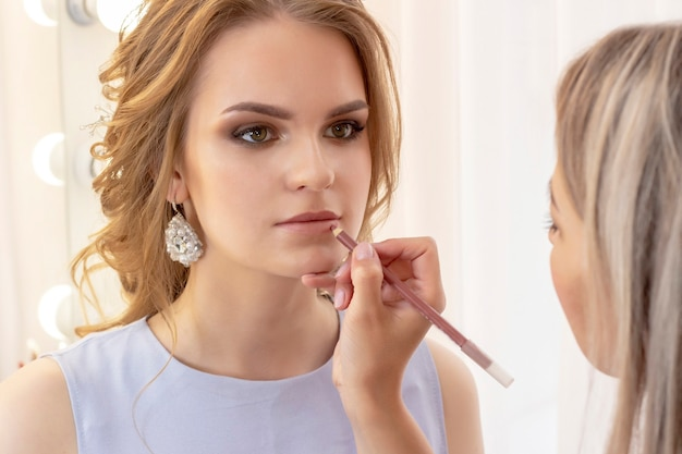 Maquiador pinta o modelo dos lábios com delineador labial. maquiagem em tons suaves de bege neutro dia