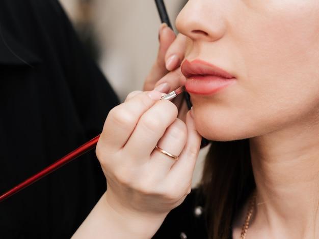 Maquiador pinta os lábios com um pincel labial para uma mulher em um salão de beleza