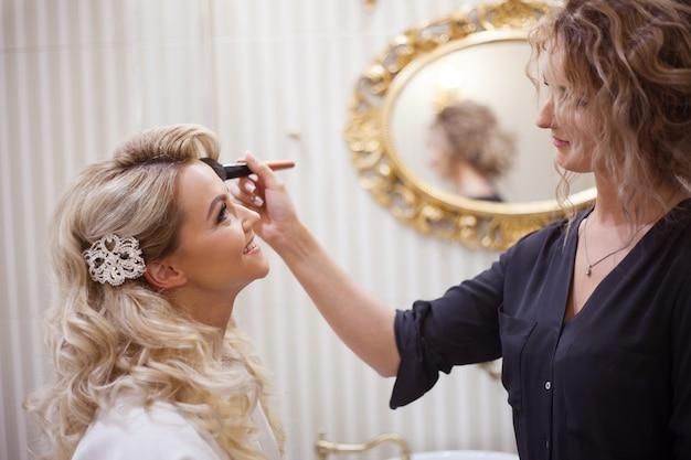 Maquiador preparando a noiva antes do casamento em uma manhã