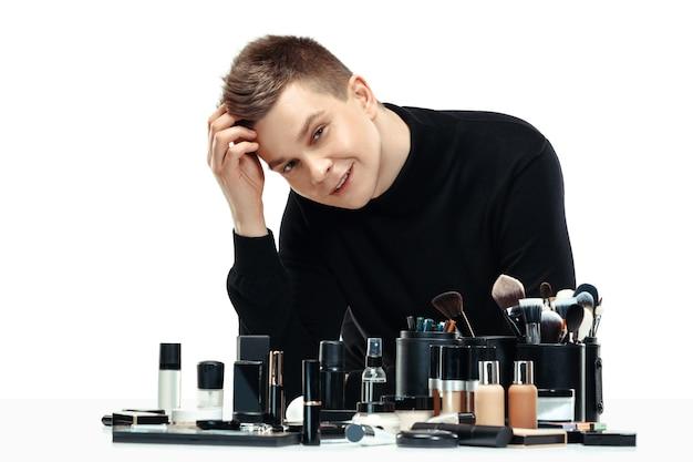 Maquiador profissional com ferramentas isoladas em branco. o homem na profissão feminina. conceito de igualdade de gênero